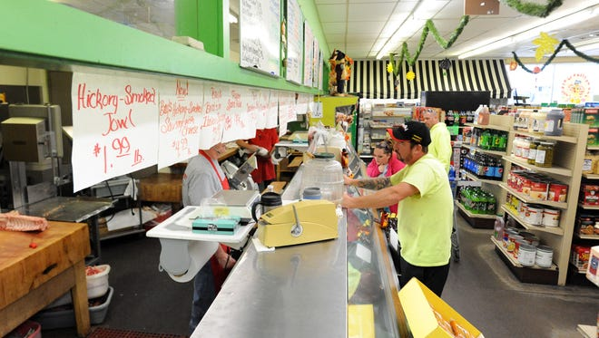Bays Food Market customers stand by the store's meat and deli counter to Friday in Lancaster. The store is not closing despite rumors that it would.