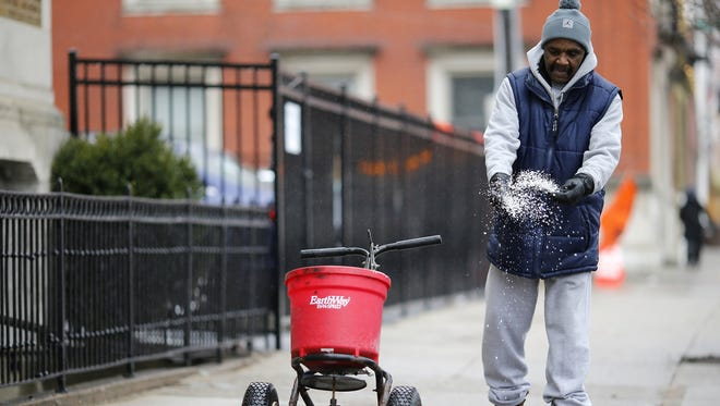 Maintenance man James McFarland spreads salt along the sidewalk on Race Street in the Over-the-Rhine neighborhood of Cincinnati on Friday, Jan. 12, 2018. As of 3 p.m. Friday projected snowfall hadn't made its way to downtown Cincinnati, but 2-4 inches of snow was still expected to fall in the evening.