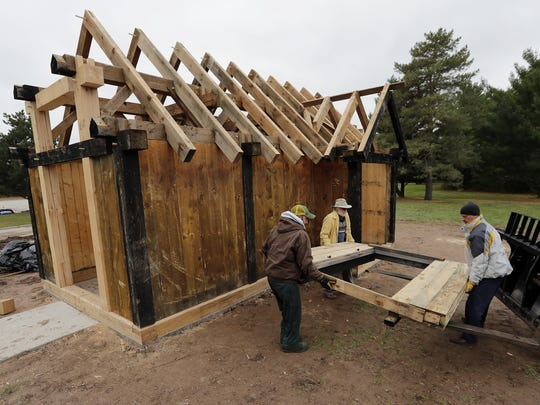 A door is unloaded outside a replica of a Viking-age house at University of Wisconsin-Green Bay on Frida. The house was donated by Owen and Elspeth Christianson who built it on their property in Stratford in 2011. Now retiring and selling the property where the house stood, the couple decided to donate it to the university where it will be used by the history department.