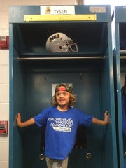 Tysen Thompson tries this football locker on for size at Mount St. Joseph University.