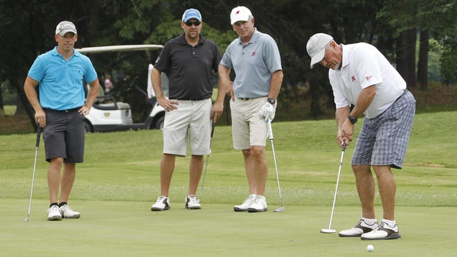 Frazier Allen, left, John Rudolph and Tom Hartz watch as Ron Jacksons putts during Governors and Chamber Community Golf Classic Friday.