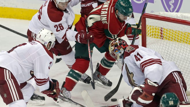 Arizona Coyotes goalie Mike Smith, right, gets some help from Keith Yandle, left, and Michael Stone as Minnesota Wild right wing Justin Fontaine tries a wrap-around shot in the third period of an NHL hockey game, Thursday, Oct. 23, 2014, in St. Paul, Minn. The Wild won 2-0.