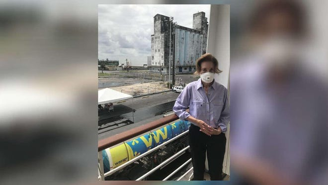 Susan Gary stands on the balcony of the cruise ship cabin where she and her husband, Brad, were confined for the fifth day Tuesday after a fellow passenger tested positive for the coronavirus. Behind her is a view of the Port of Recife in northeastern Brazil.