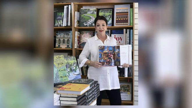 "Candice Cohen, shown in March with a copy of ""Le Manoir Aux Quat'Saisons"" is reopening her Palm Beach Bookstore on Monday."
