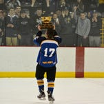 Maine-Endwell's Colin Wenzel hoists the Broome County High School Hockey Association's championship trophy in front of his team's fans following M-E's 4-1 victory over Vestal in the title game Saturday at the SUNY Broome Ice Center.