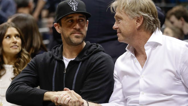 Milwaukee Bucks owner Wes Edens and Green Bay Packers QB Aaron Rodgers shake hands during the Bucks- Celtics game Friday. Rodgers joined the Bucks' ownership group.