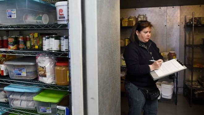 Food inspector Ivonne Rodriguez takes notes at Ruby's Kitchen during an inspection on Feb. 10 in Nashville.