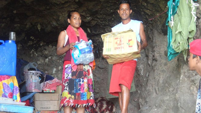 A grateful couple holds water and tea donated by people on Guam and distributed by the Ayuda Foundation, which collected the donated goods and worked to ship them to and distribute them in Chuuk.