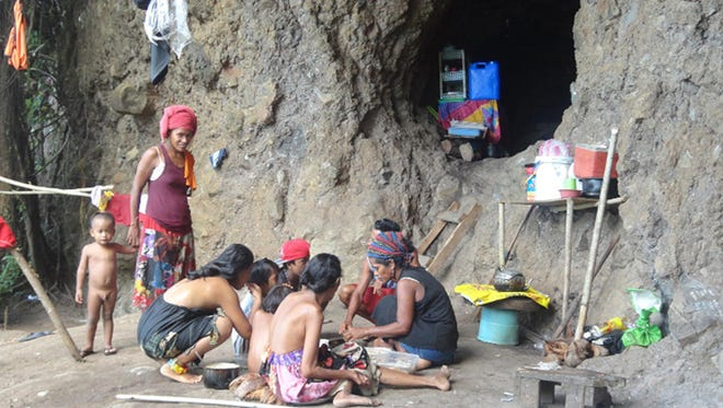 A family works together outside its makeshift home in a cave in Chuuk.