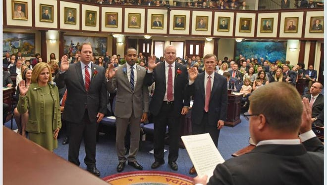 Jayer Williamson, second from left, takes the oath of office on the floor of the Florida House of Representatives on Nov. 22. With Williamson, from left: Loranne Ausley, a Democrat from Tallahassee; Ramon Alexander, a Democrat from Tallahassee; Mel Ponder, a Republican from Destin; and Frank White, a Republican from Pensacola.