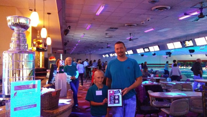 Ava, a special helper at last year's Bowling for Backpacks event, presents the door prize (2 Red Wings tickets and a parking pass) to the lucky winner, Tim Mulvany.