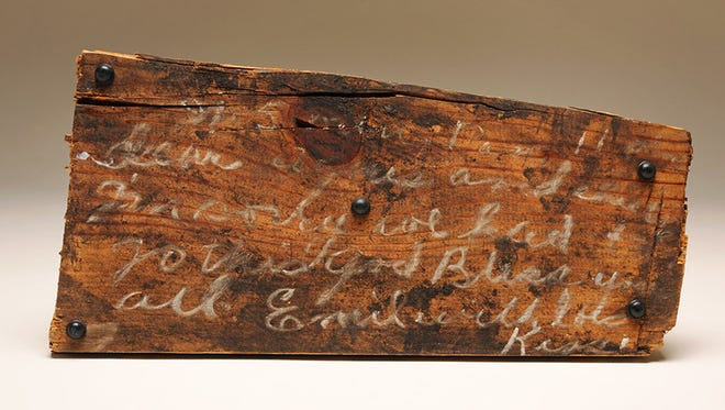 """A piece of wood with a chalk message from a miner trapped in the Smith Mine. At 8 a.m., Saturday, February 27, 1943, Emil Anderson and seventy-six other coal miners entered Smith Mine #3 near the community of Bearcreek. One hour and thirty-seven minutes later, employees close to the surface of the mine felt an enormous pressure in their ears, followed by a powerful gust of air filled with soot and debris exploding past them. Only three workers escaped from the mine. Within its depths, thirty men died instantly from the forceful blast and another forty-four soon suffocated. Anderson was part of this latter group. In the short time he had remaining, he used the materials he had available to leave his family this message on the lid of a dynamite box: """"It's 5 minutes pass [sic] 11 o'clock Agnes and children I'm sorry we had to go this way God bless you all Emil with lots [of] kisse[s]."""" This fragile letter."""