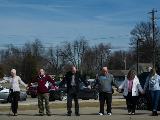 Members of the community join hands in prayer outside