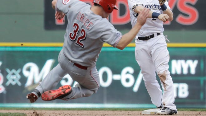 Reds right fielder Jay Bruce is safe at second as the Brewers' Scooter Gennett tries to turn a double play on a bases-loaded ball hit by Adam Duvall during the ninth inning of their game on Saturday in Milwaukee. Bruce was originally ruled out, but was called safe after a review. Duvall was out at first as the Reds scored a run.