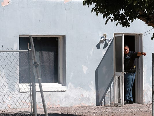 A police supervisor stands in the doorway of a home at the 200 block of Candelaria in El Paso's Lower Valley on Friday.