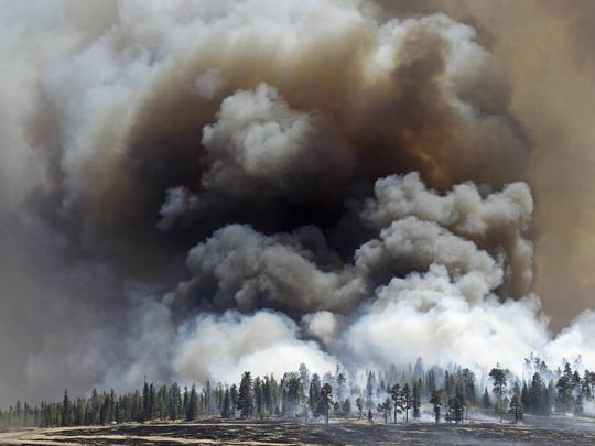 Smoke rises as firefighters battle the Wallow Fire