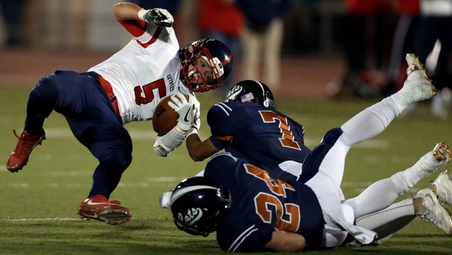 Cienega's Terrell Hayward (7) manages to drag down against Centennial's Alex Escobar (5) after he squirted into the defensive secondary in the second quarter of their 5A state semifinal game at Tucson High School, Friday, November 18, 2016, Tucson.