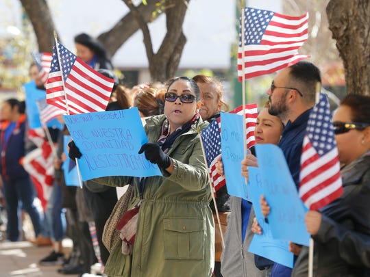 Protesters hold up signs and American flags Friday at San Jacinto Plaza in Downtown El Paso. Dozens of immigrant families held a peaceful protest to mark their dedication to upholding human dignity and human rights and to protest the inauguration of the 45th U.S. president, Donald Trump.