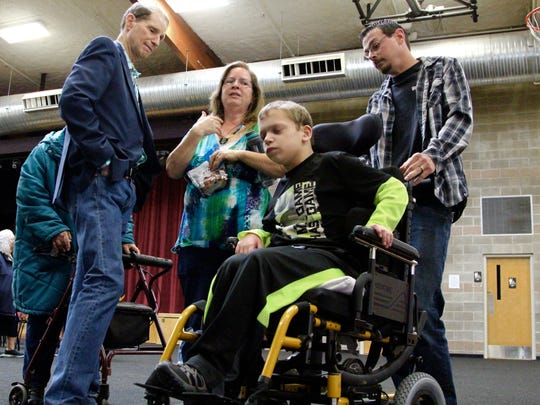 United States Senator Ron Wyden speaks with Patrice Qualman, of Grand Ronde, about her fears of losing health care for her 14-year-old son Cody, who has a rare genetic disorder.