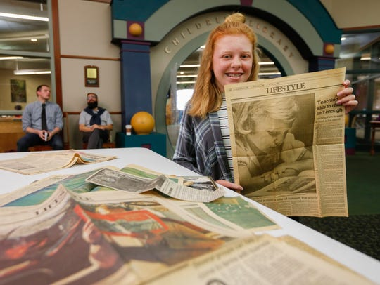 "Bailey Birtciel, 12, holds up a photo of her mom, Ashley Birtciel, during the Springfield News-Leader's ""More to the Story"" event at the Library Center on Saturday, Nov. 4, 2017."