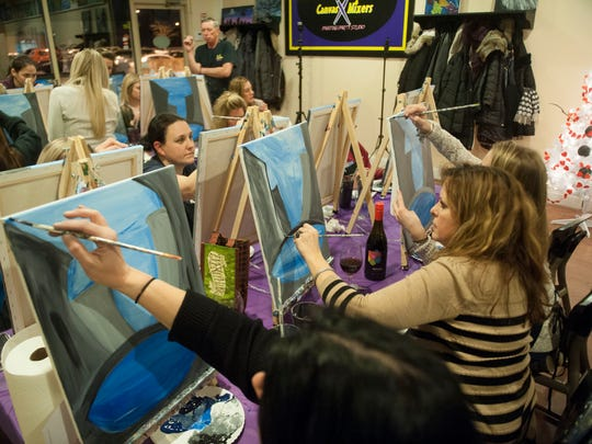 A group of women attend a step-by-step group painting lesson at Canvas Mixers Painting Party Studio in Marlton. Painting parties are a big hit for Girls Nights Out.