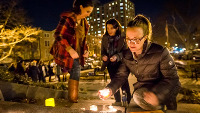Theresa Sullivan places a candle down as she lights them with other attendees at a vigil to show solidarity with refugees near the Soldiers and Sailors Monument in Wilmington on Wednesday night.