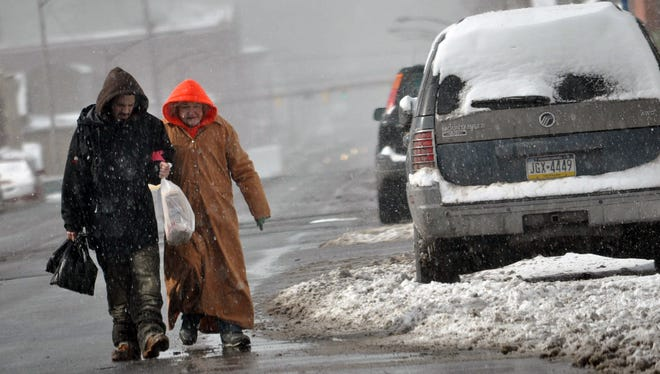 A couple helps one another walk after a snowstorm dropped 3 inches in Hazleton, Pa., on Jan. 30, 2015. Another winter storm is set to sweep across the northern tier Sunday and Monday.