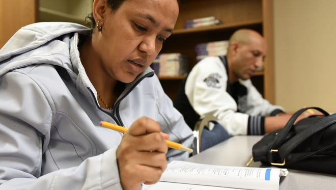 Tiruwork Hailu and Michael Bouretsion work on exercises during a bridges program class at Killian Community College in Sioux Falls, S.D., Thursday, March 31, 2015.
