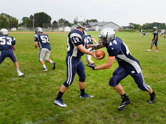 Eden Vally-Watkins quarterback Jack Bates hands the ball off to running back Dominic Schlangen during practice Friday, Aug. 18, in Eden Valley.
