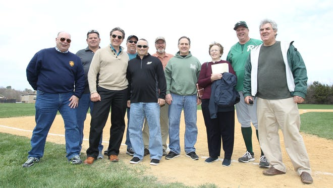 Members of the FDR High School's 1977 HVBC Championship baseball team gather at third base for a commemorative ceremony prior to a varsity baseball game against North Rockland at FDR High School in Hyde Park on Saturday, April 15, 2017.