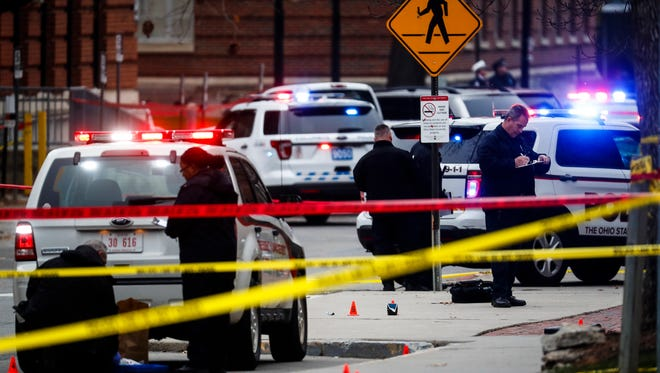Crime scene investigators collect evidence from the pavement as police respond to an attack on campus at Ohio State University, Monday, Nov. 28, 2016, in Columbus, Ohio.
