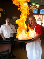 Rigo Ochoa of Yanni's Grill and Vineyard in Ankeny fires a pan of Saganaki, a Greek appetizer, on Friday, April 17, 2015.
