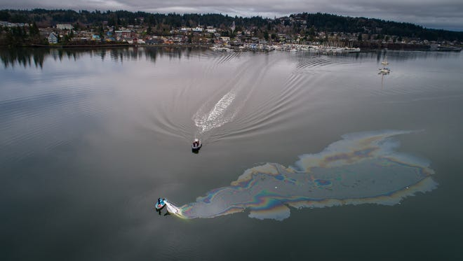 Emergency crews respond to a vessel sinking in Liberty Bay Sunday morning. The motor boat's lone occupant was able to escape in a dinghy.