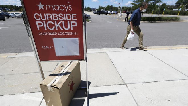 A man wears a mask as he walks past a curbside pickup sign at Macy's department store in Vernon Hills, Ill., Thursday, June 25, 2020. Macy's is cutting roughly 4,000 back-office and management jobs as COVID-19 continues to hurt its bottom line.