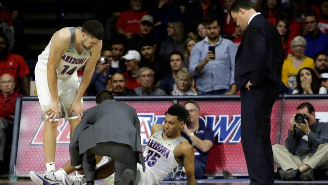 Arizona trainer looks at Arizona guard Allonzo Trier (35) as Dusan Ristic (14) and head coach Sean Miller look on in the second half during an NCAA college basketball game against North Dakota State, Monday, Dec 18, 2017, in Tucson, Ariz. Arizona defeated North Dakota State 83-53.