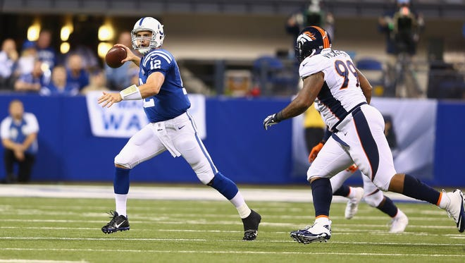 Andrew Luck of the Indianapolis Colts looks to pass under pressure from Kevin Vickerson  of the Denver Broncos at Lucas Oil Stadium on October 20, 2013 in Indianapolis, Indiana.