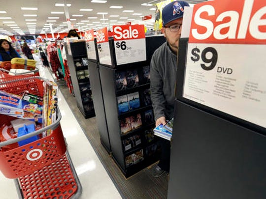 FILE - In this Friday, Nov. 25, 2016, file photo, Paul Poirier shops for sales at a Target store, in Wilmington, Mass. Retailers are pushing promotions and other enticements for the final stretch of the holiday season as new numbers show that shoppers are spending at a decent, but a tad slower rate compared to last year.