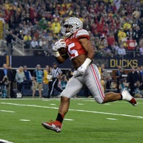 Ohio State Buckeyes running back Ezekiel Elliott (15) scores on a 33-yard touchdown run in the first quarter against the Oregon Ducks in the 2015 CFP National Championship Game at AT&T Stadium. Ohio State defeated Oregon 42-20.