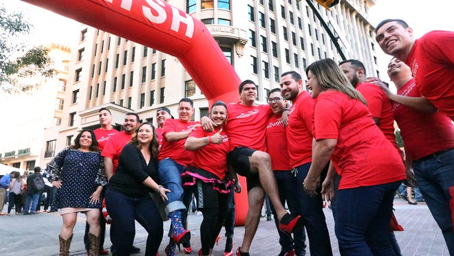 Male employees of Wells Fargo show off their red women's shoes at the start of the YWCA El Paso del Norte's 8th annual Walk A Mile In Her Shoes fundraiser Thursday Downtown.