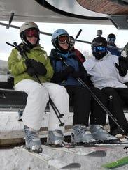 Skiers hop on ski lift at Granite Peak Ski Area.
