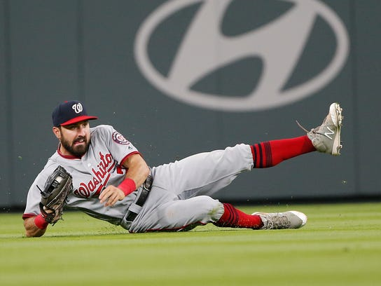 Washington Nationals left fielder Adam Eaton falls after catching a fly ball hit by Atlanta Braves' Ender Inciarte during the seventh inning of a baseball game Thursday, April 20, 2017, in Atlanta. Washington won 3-2. (AP Photo/John Bazemore)