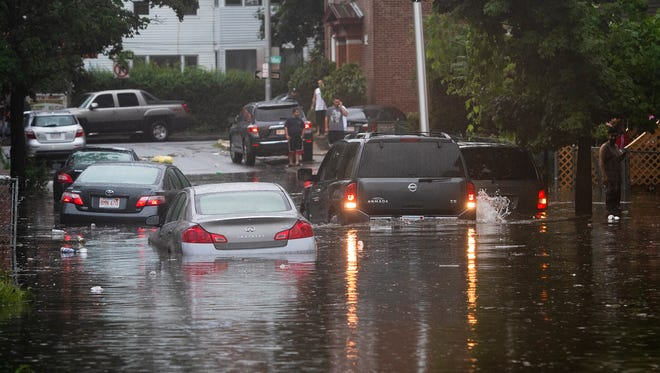 Vehicles are stranded on a Worcester, Mass., street during flash flooding from storms Tuesday, July 17, 2018. More storms and floods are forecast this week across the eastern U.S.