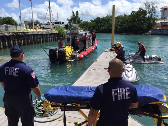 Guam Fire Department personnel transport the recovered