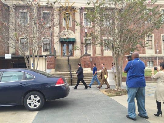 Chris Few (center, in blue jeans and blue shirt) walks