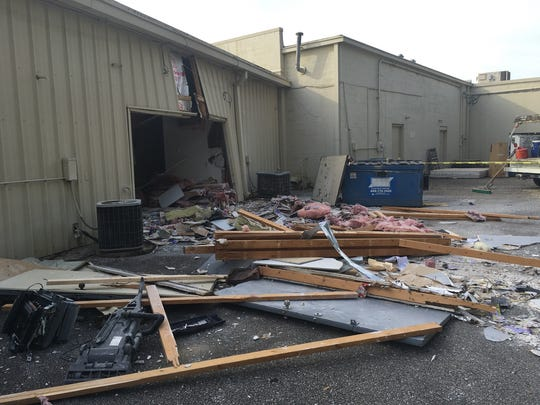 Debris from inside Advance Tax Services is strewn behind the business at North Davis Highway and West Fairfield Drive after a car ran through the building at around midnight Sunday, crashing through the front entrance and emerging through the back.