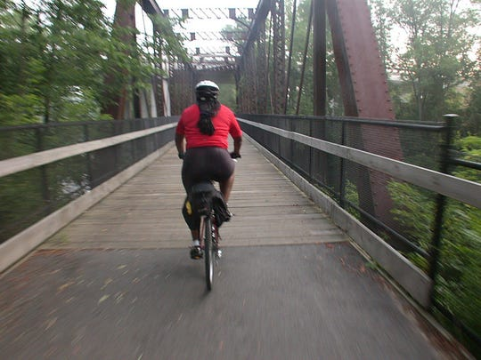 Cassandra crosses a bridge riding the Michigander on her second day out biking from Rockford.