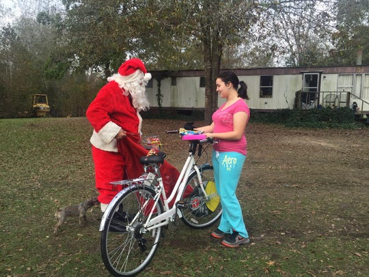 Santa Claus warned 12-year-old Cheyenne about speeding on her new bike. Santa and others from the Grant Parish Sheriff's Office spent Wednesday morning delivering presents and food to four families across the parish.