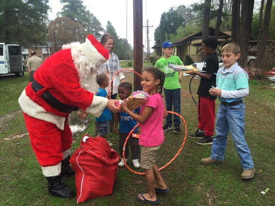 Trinity (center), 6, holds a hula-hoop and other presents given to her Wednesday by Santa Claus. She and her brothers got presents delivered to them by the Grant Parish Sheriff's Office.