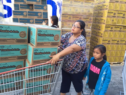 In this Jan. 2, 2016, file photo, Guam Girl Scouts members and volunteers sort the annual shipment of Girl Scout cookies at Tamuning Cost-U-Less.