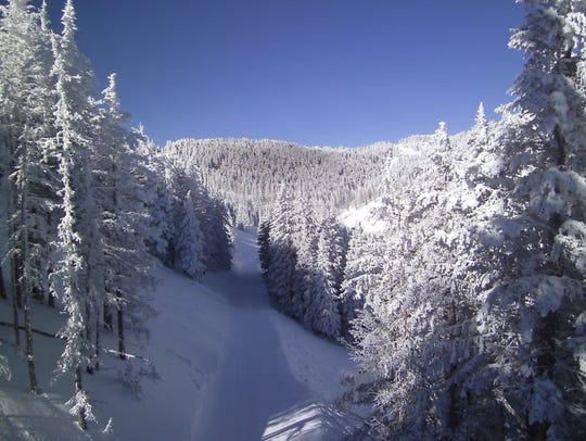 Crossing above Sierra Blanca Trail on Chair One, skiers